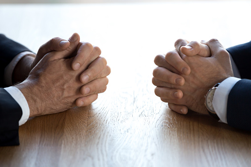 close up of hands of business men with their hands clasped.